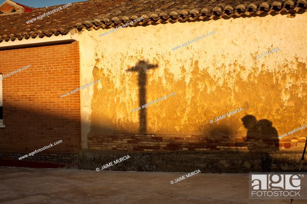 Stock Photo: Shadow of a pilgrim and cross on a wall along the Camino de Santiago.