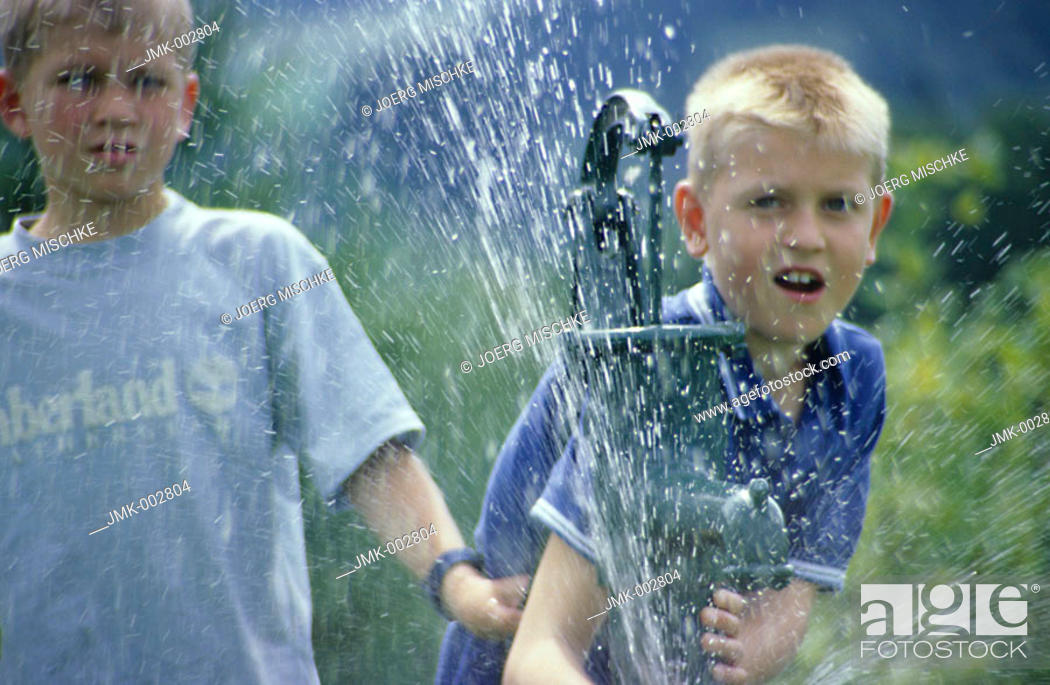 Stock Photo: Two children, boys, 5-10 years old, playing in the garden with water.