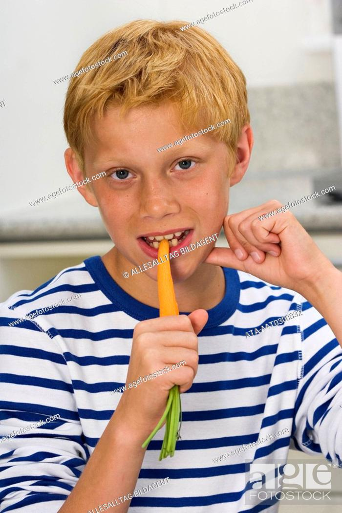 Photo de stock: Boy nibbling carrot.