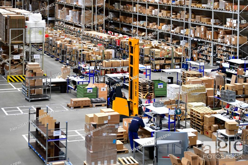 Stock Photo: 16 April 2020, Brandenburg, Großbeeren: A Jungheinrich electric high-bay truck drives between high-bay racks and packing tables at the logistics service.