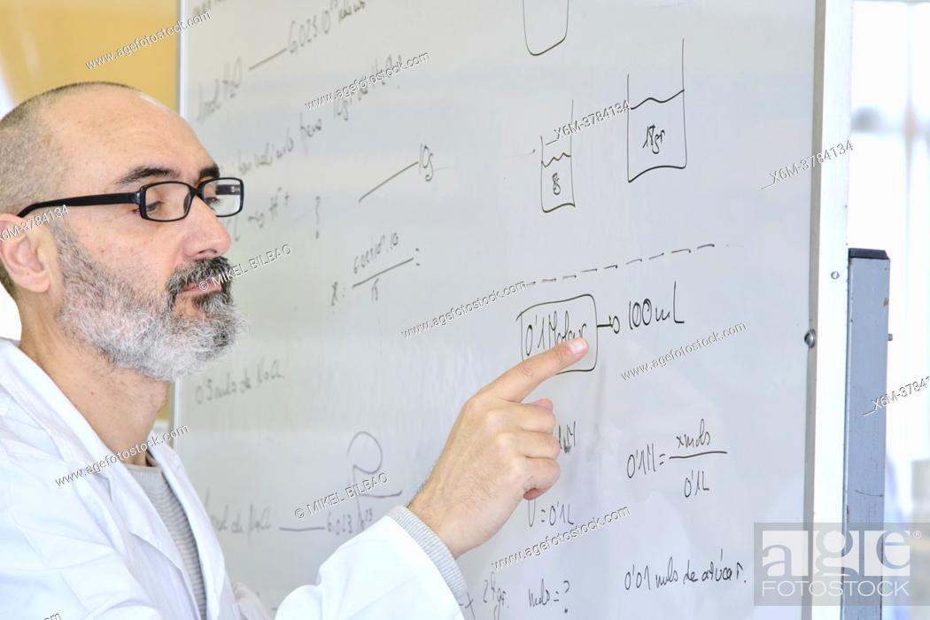 Stock Photo: Male teacher in his 50's in a lab coat explaining chemistry on a blackboard. Basque Country, Spain, Europe.
