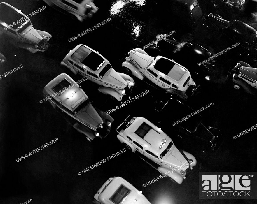 Stock Photo: New York, New York: c. 1935.Taxis doing a thriving business on a rainy evening in Manhattan.