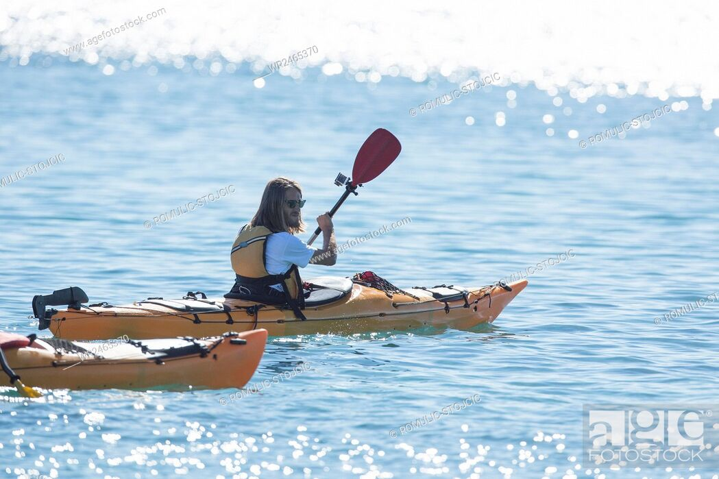 Stock Photo: Mid adult man kayaking on river in bright sunshine.