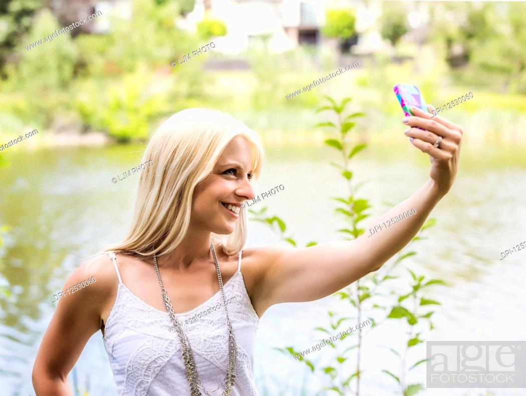 Stock Photo: A beautiful young woman taking a self-portrait while enjoying her alone time in a park with a manmade lake; Edmonton, Alberta, Canada.