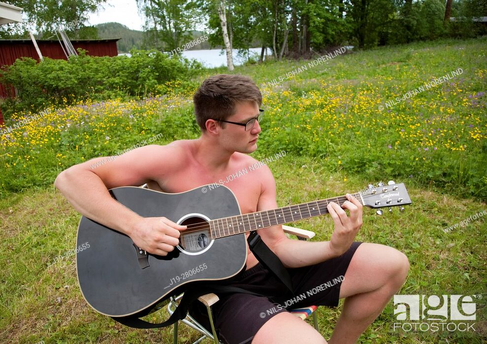 Stock Photo: Man playing guitar outdoors, countryside of northern Sweden.