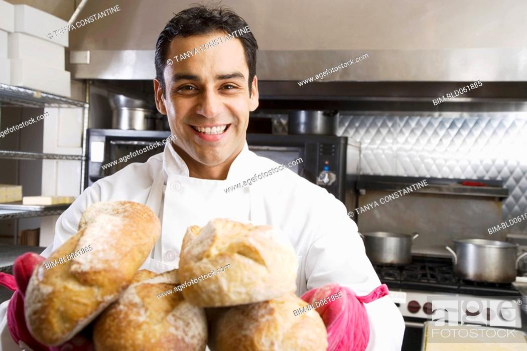 Stock Photo: Hispanic male baker holding fresh bread.