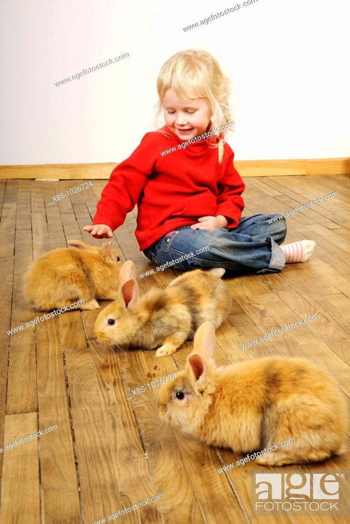 Stock Photo: Stock photo of a four year old girl playing with her pet rabbits on a wooden floor.