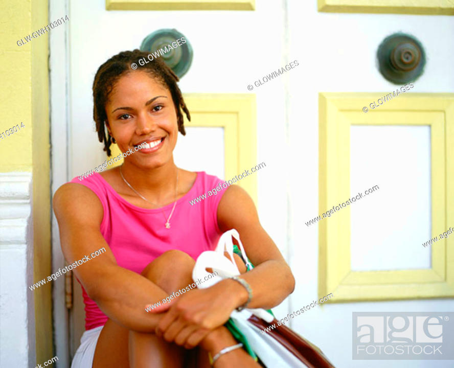 Stock Photo: Portrait of a young woman sitting and hugging her knees, Bermuda.