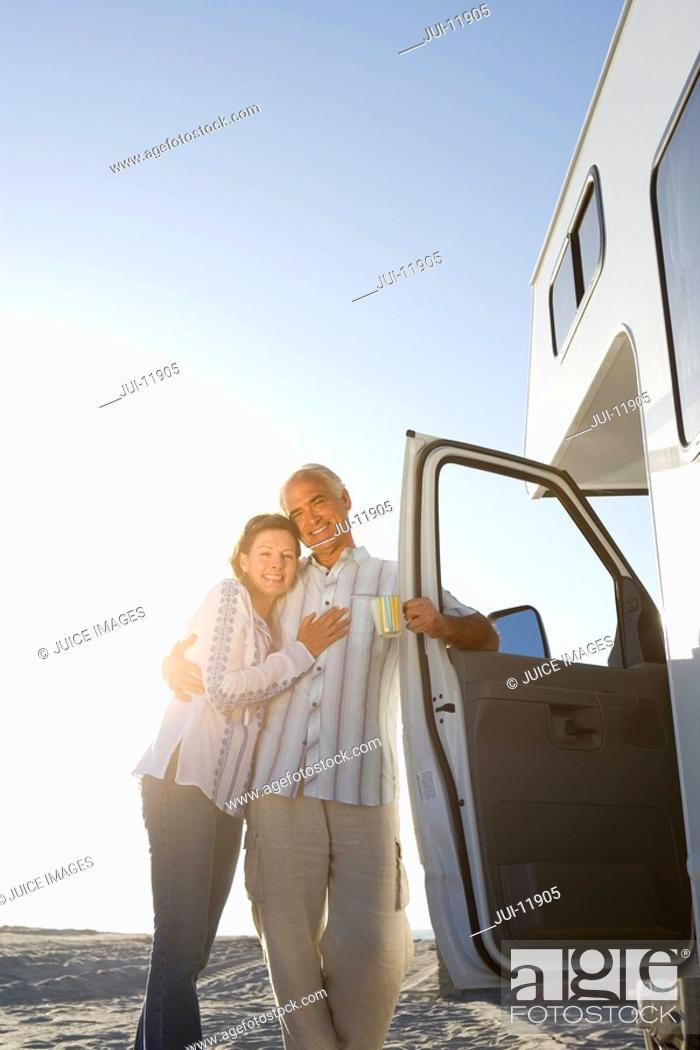 Stock Photo: Mature couple arm in arm by motor home on beach, smiling, low angle view sun flare.