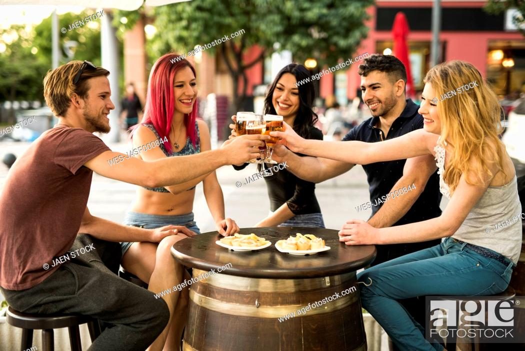 Stock Photo: Friends in a bar toasting with beer glasses.