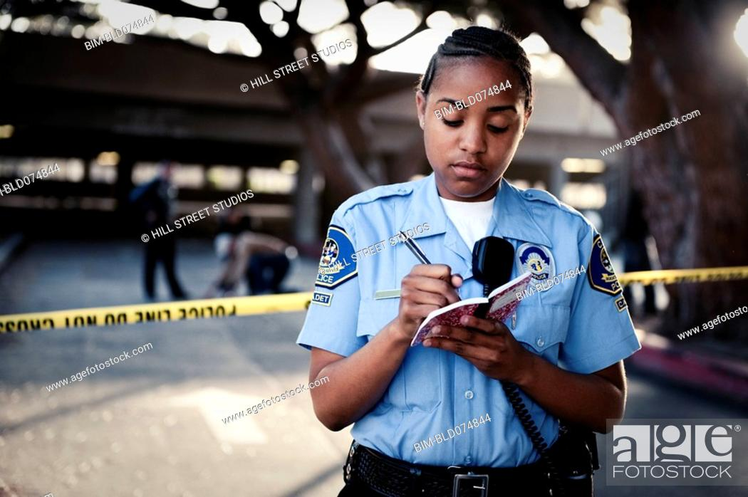 Stock Photo: African policewoman writing in notebook.