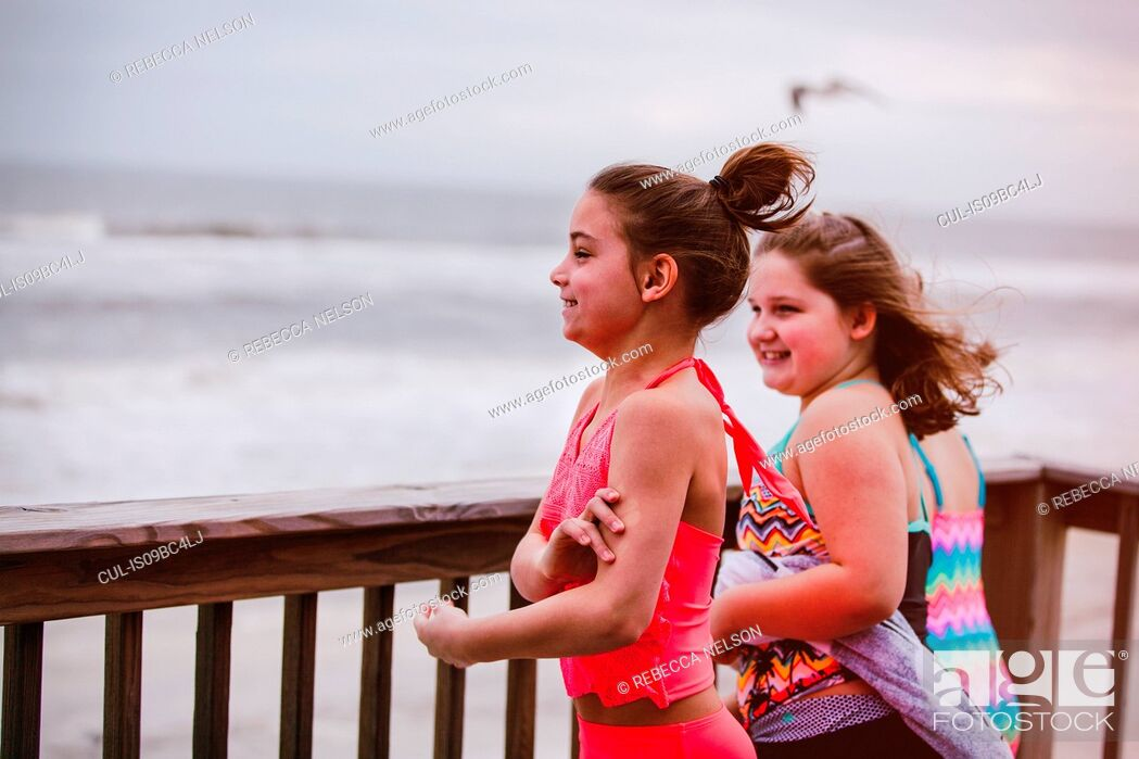 Stock Photo: Three girls looking out at sea from balcony, Dauphin Island, Alabama, USA.