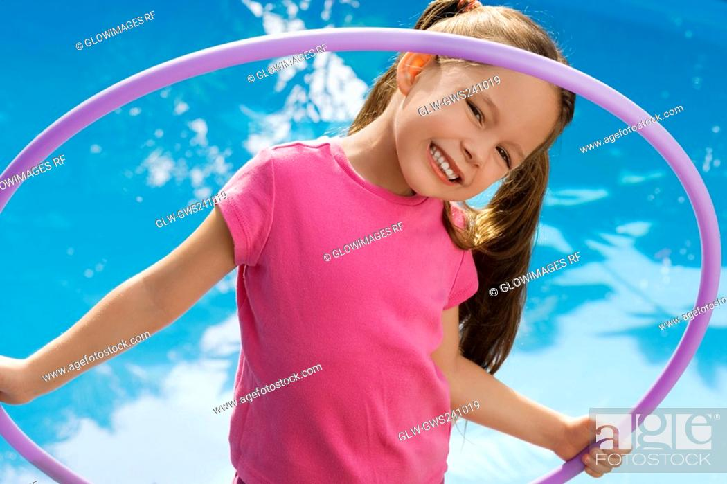 Stock Photo: Portrait of a girl holding a plastic hoop and smiling.