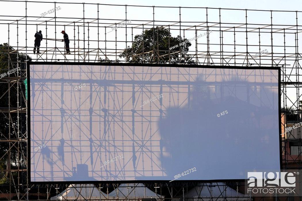 Photo de stock: Two men installing a huge open-air screen, Djemaa el-Fna, Marrakech, Morocco, Africa.