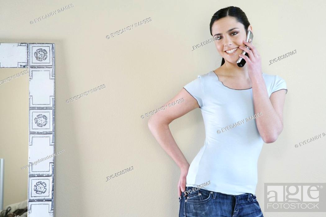 Stock Photo: Young woman standing, smiling with a cell phone.