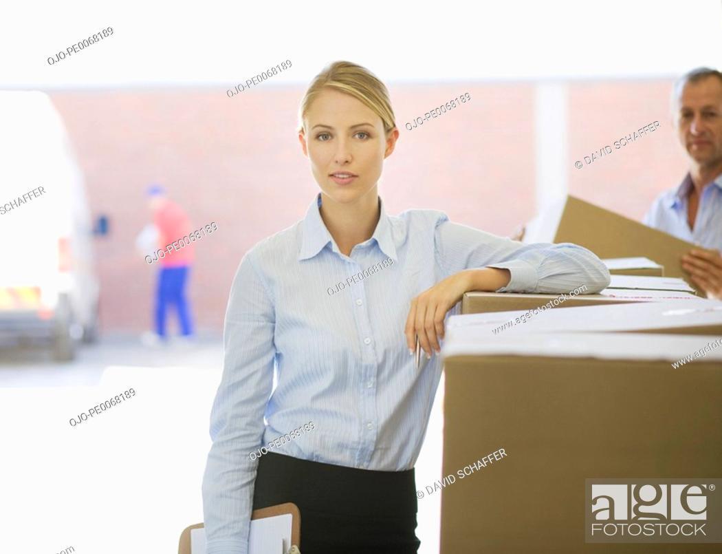 Stock Photo: Businesswoman leaning on cardboard box.