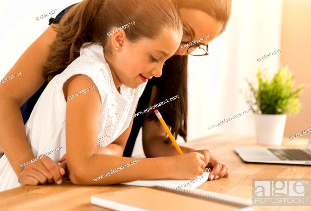 Stock Photo: Mother and daugther at home doing homework together.