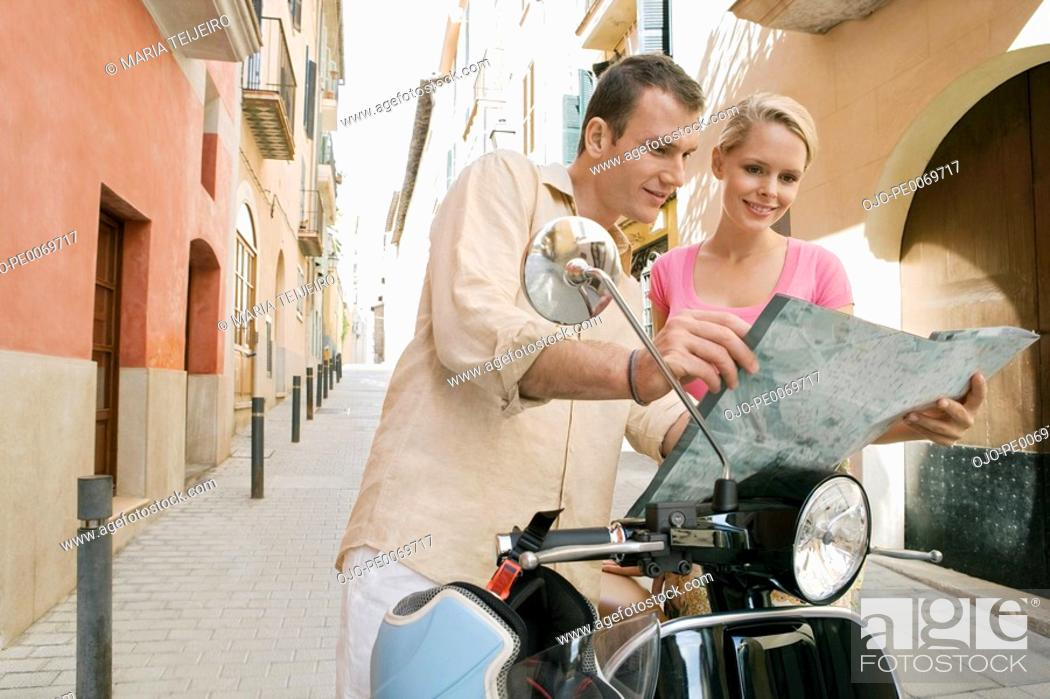 Stock Photo: Man and woman with scooter reading map.
