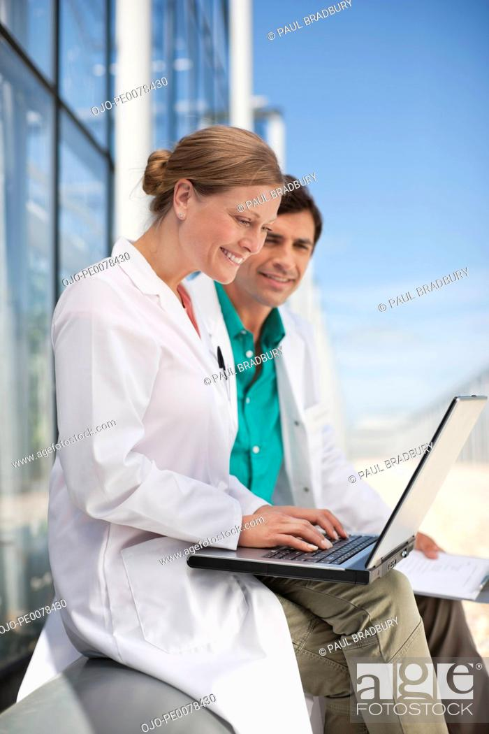 Stock Photo: Scientists using laptop outdoors.