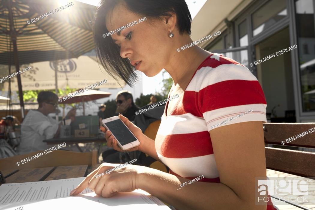 Imagen: woman checking menu card in outdoor restaurant, at Herrenchiemsee, Chiemsee, Bavaria, Germany.