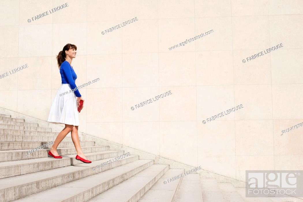 Stock Photo: Woman moving down steps, Paris, Ile-de-France, France.
