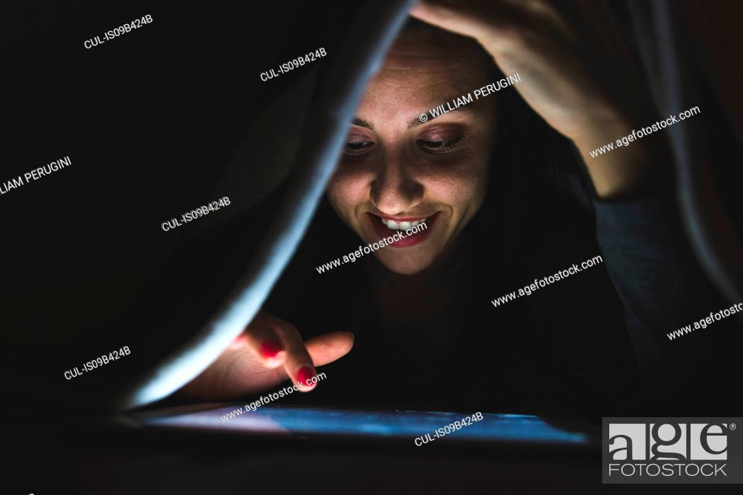 Stock Photo: Young woman under blanket using digital tablet touchscreen in darkness.