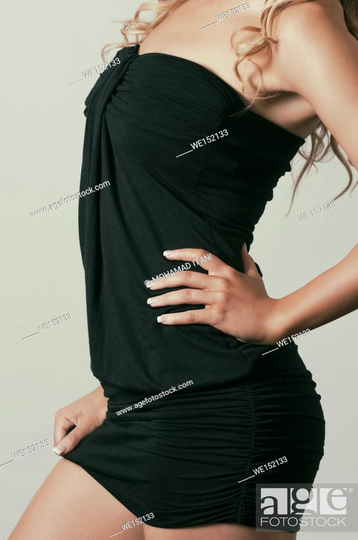 Stock Photo: Close up of a sexy young woman wearing a short black dress hand on hips.