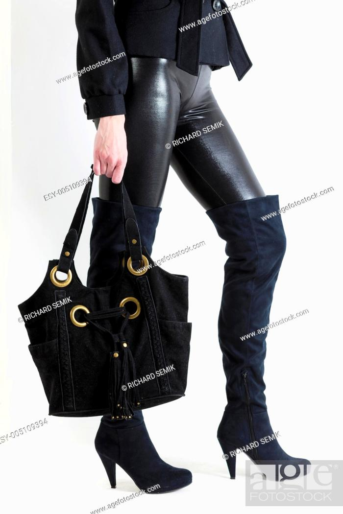 Stock Photo: detail of standing woman wearing black boots with a handbag.
