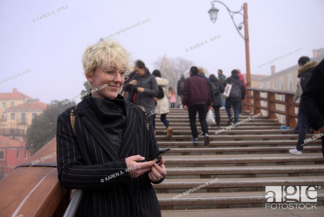 Stock Photo: Stylish young woman in pin-stripe coat, wire-rim glasses, blond-white short hair, on Accademia bridge with little smile holding phone, foggy day, Venice, Italy.