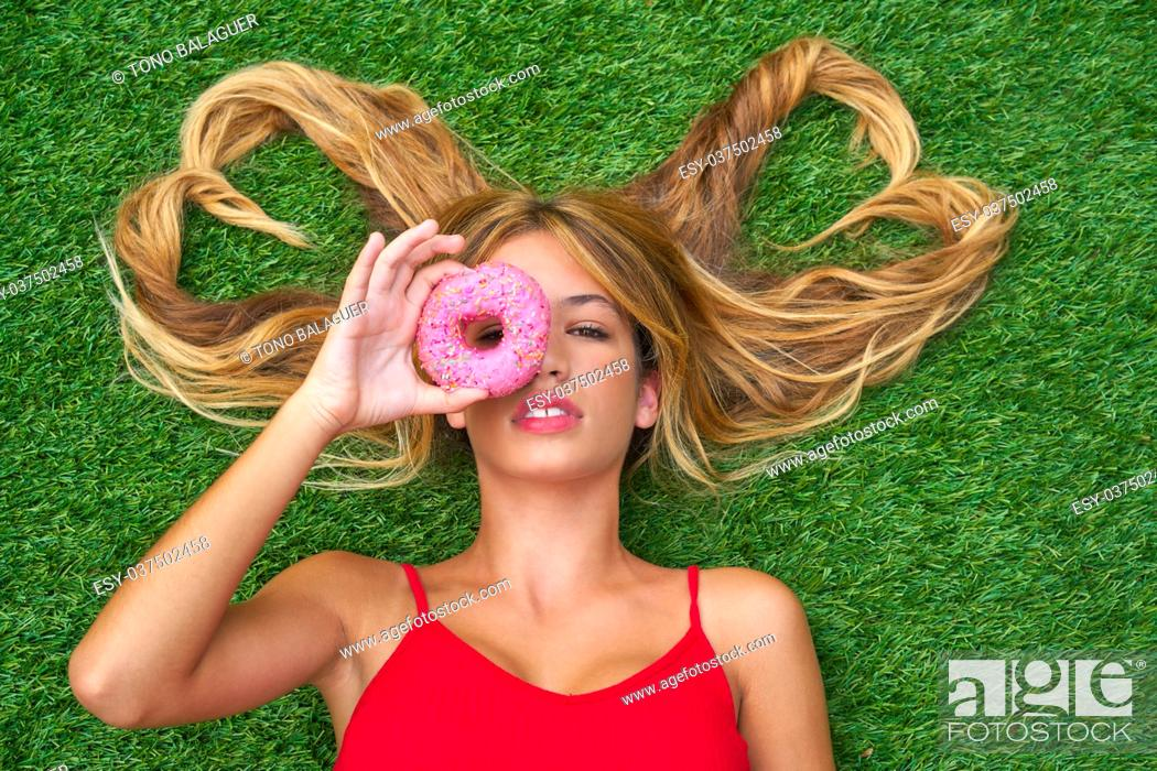 Imagen: Blond teen girl with hair heart shapes lying down on turf with donuts on eye.