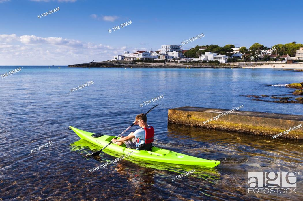 Stock Photo: A teenage boy in a Kayak at Punta Prima , Menorca , Balearic Islands , Spain.