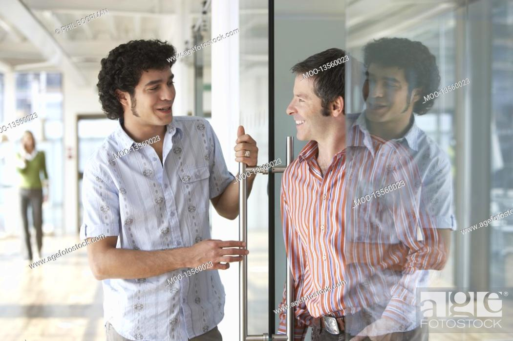 Stock Photo: Two office workers talking at glass door in office.
