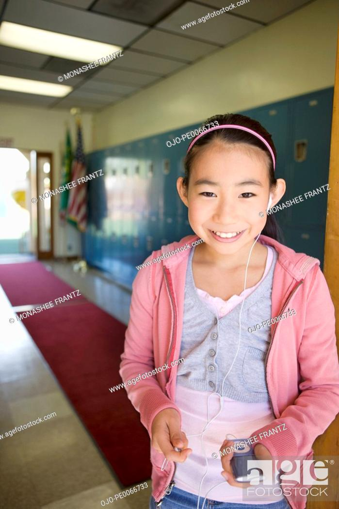 Stock Photo: Girl listening to mp3 player in school hallway.