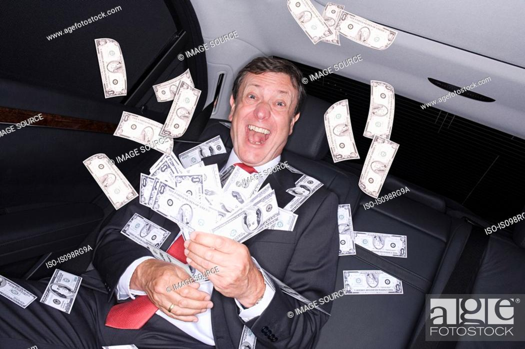 Stock Photo: Businessman in car with bank notes.