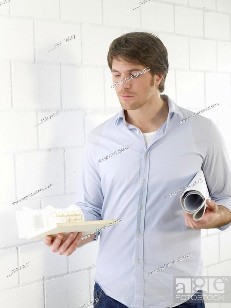 Stock Photo: Mann holding a small model house.