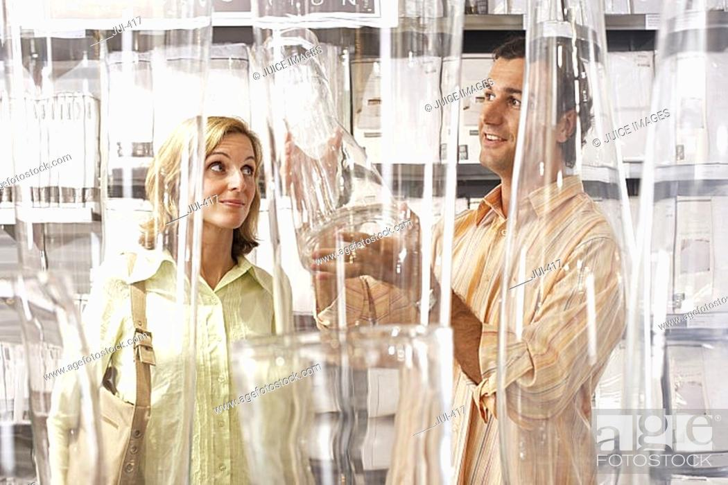 Stock Photo: Couple shopping for glass vases in department store, woman raising eyebrows, man smiling.
