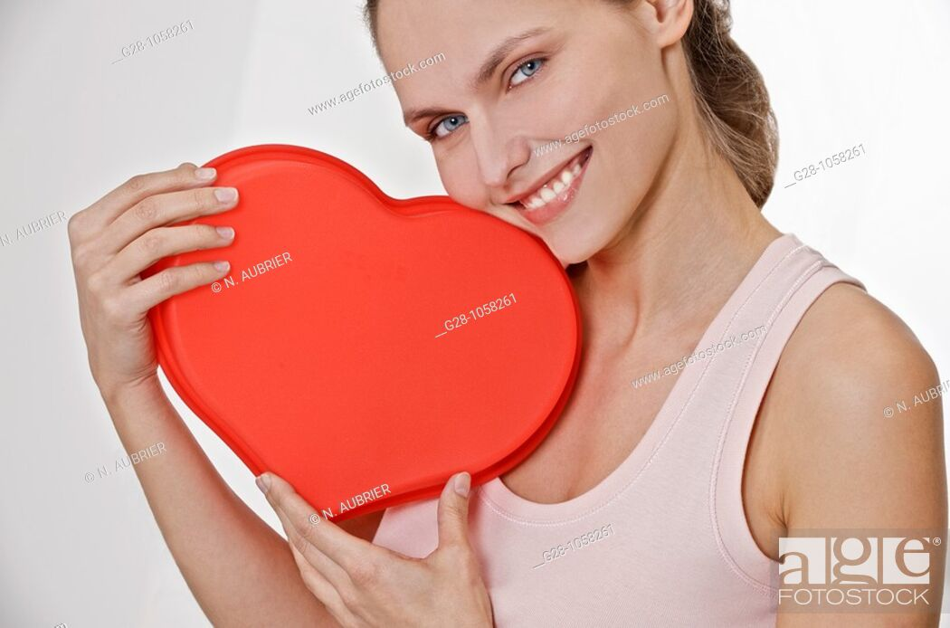 Stock Photo: young smiling woman holding a red heart in front of her.
