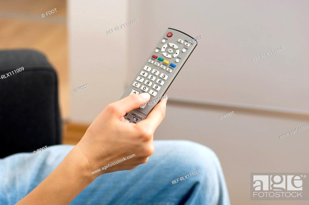 Stock Photo: Woman holding TV remote control.