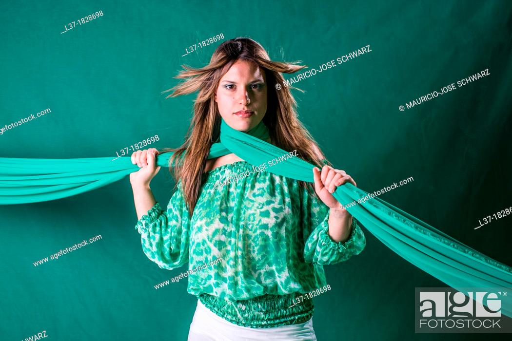 Stock Photo: Young woman in green holding a scarf around her neck.