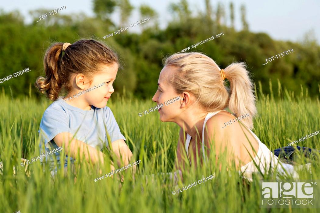 Stock Photo: A young girl and a woman relaxing in a field together.
