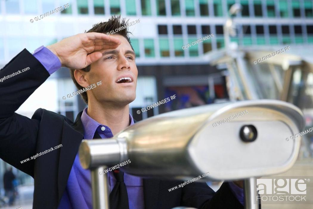 Stock Photo: Close-up of a businessman with coin-operated binoculars in front of him.