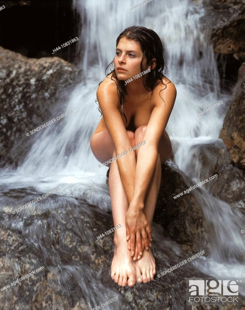 Nude woman under a waterfall that would