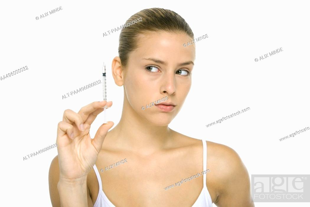 Stock Photo: Young woman looking at syringe, close-up.