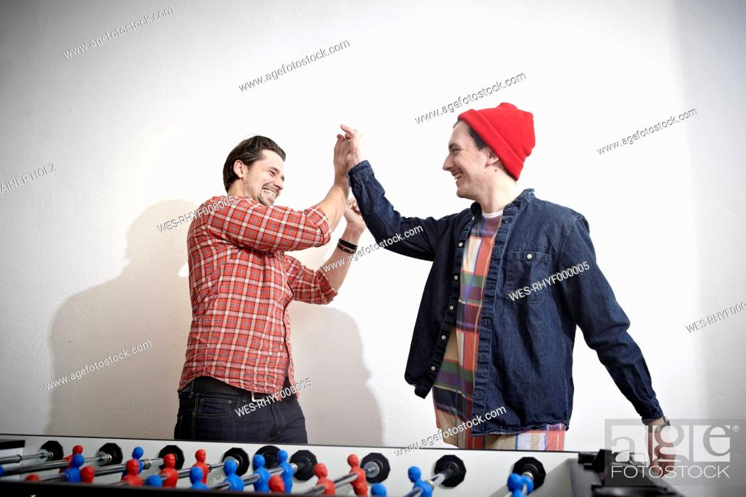 Stock Photo: Germany, Cologne, Young men playing table soccer, smiling.
