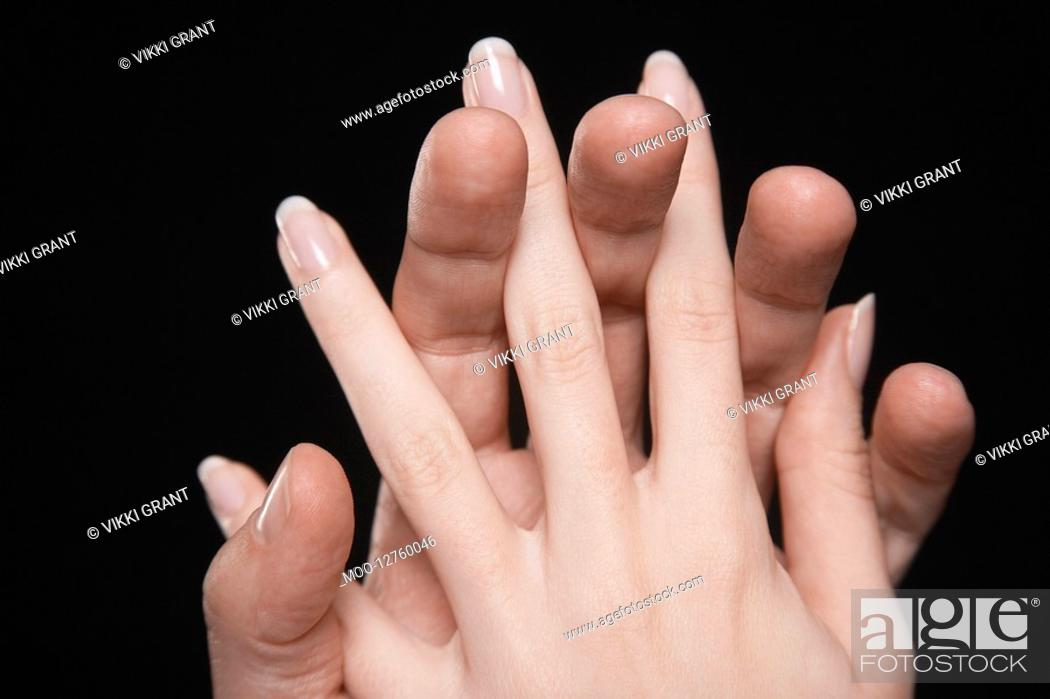 Stock Photo: Young couple with fingers interlocked close-up of hands.