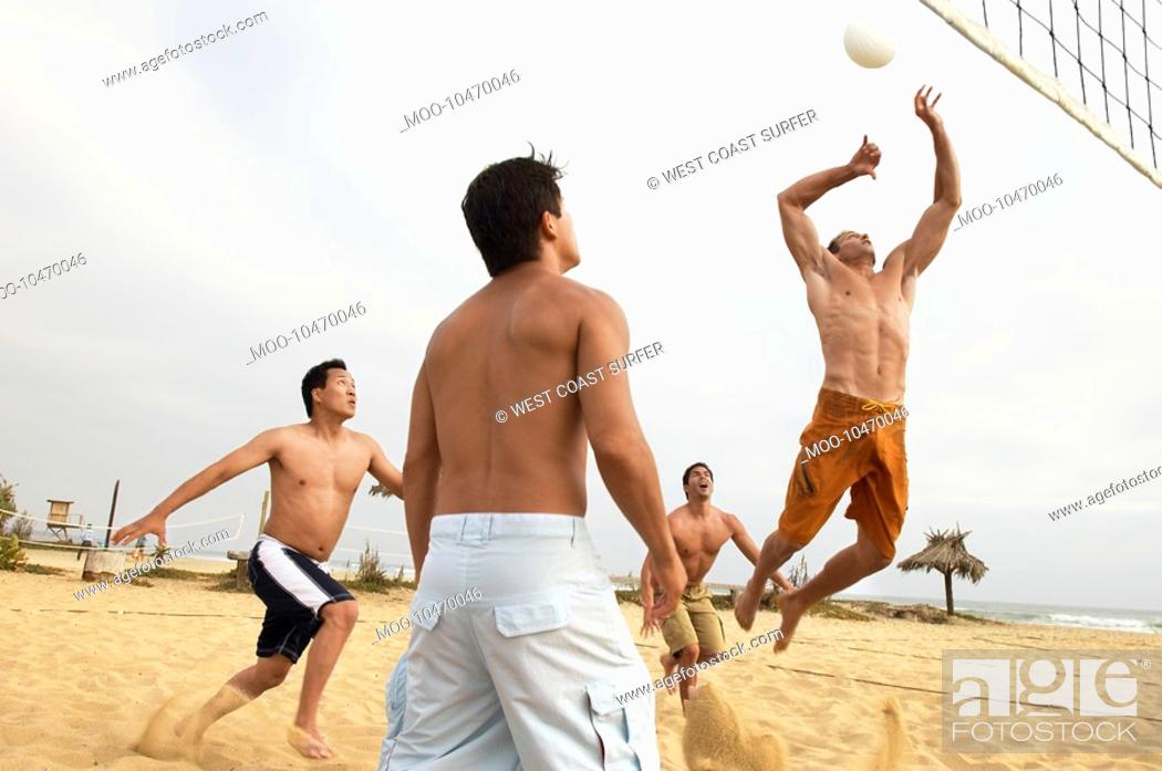 Stock Photo: Men Playing Volleyball on beach.