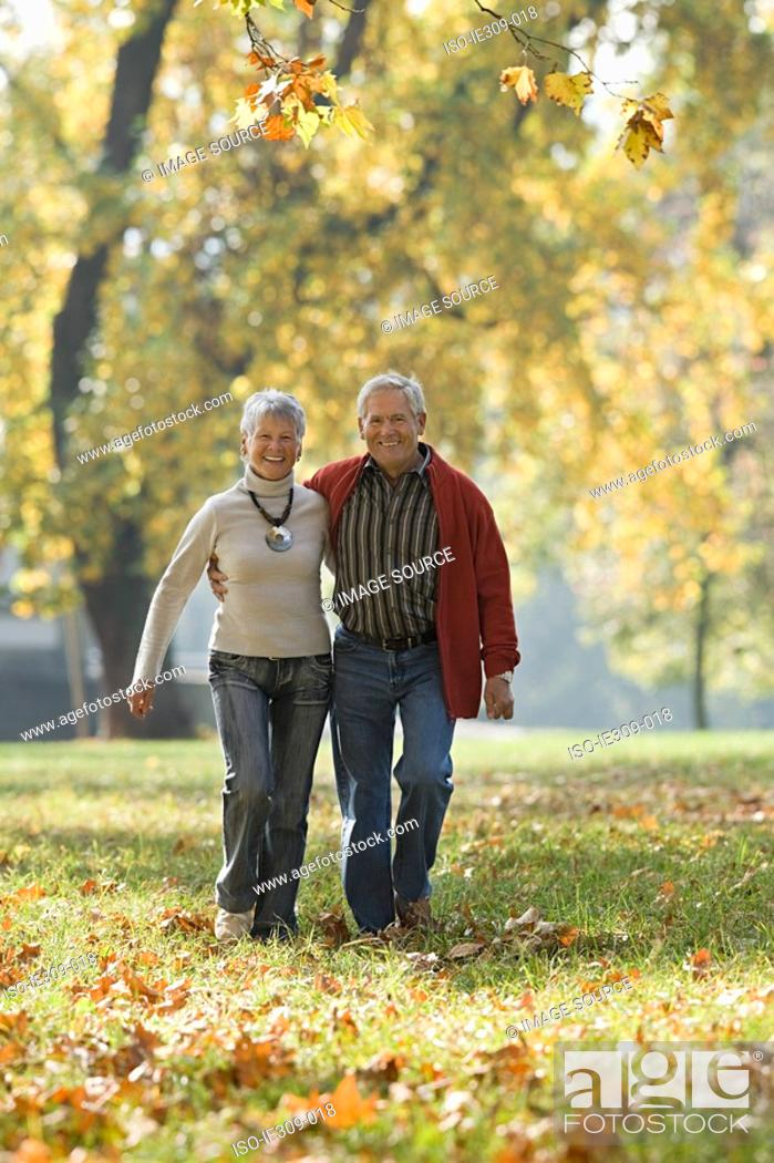 Stock Photo: Senior couple walking in a park.