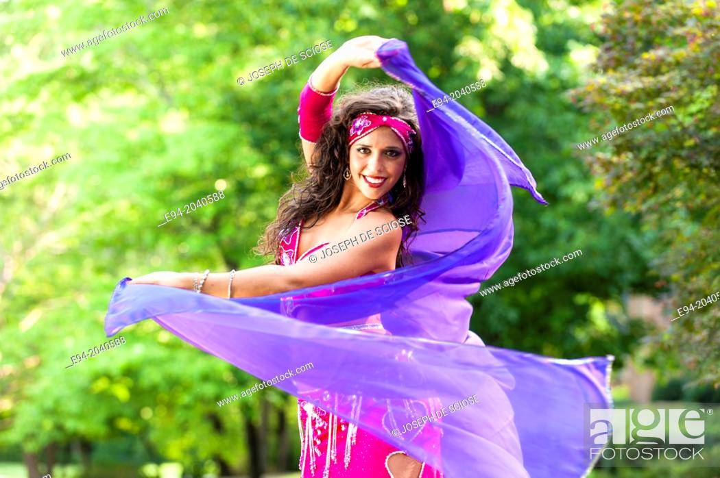 Stock Photo: A 23 year old brunette woman in costume belly dancing outdoors.