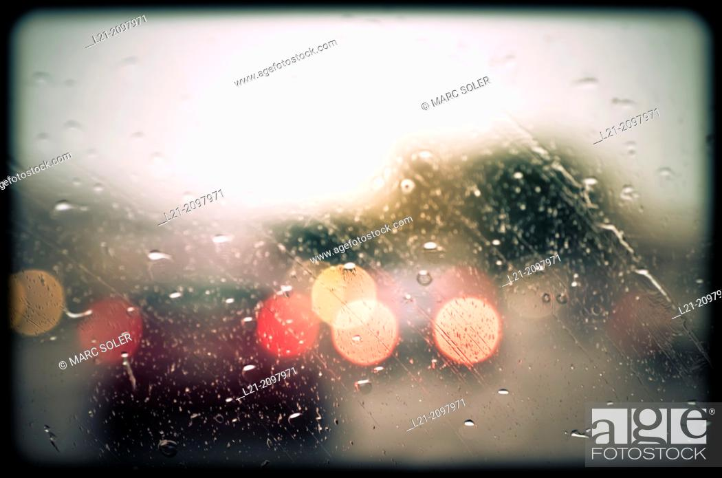 Stock Photo: Rain drops on windshield. Blurred view of cars.