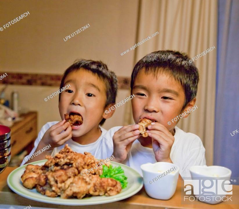 Stock Photo: Boys eating fried chicken, Japan.